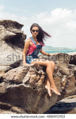 73c9770493 Sexy woman in jeans overall and pink t-shirt sit on big stone at rock