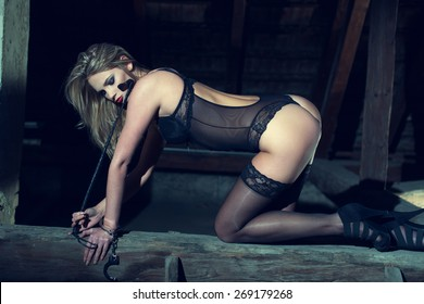 Sexy woman kneeling on the timber in barn at night, sensuality and bdsm