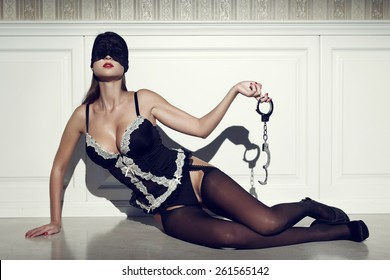 Sexy woman in lace eye cover with handcuffs, posing on floor at vintage wall