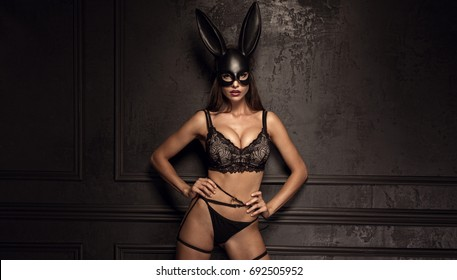 Sexy woman with large breasts wearing a black mask Easter bunny standing on a black background and looks very sensually