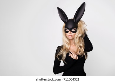 Sexy woman with large breasts wearing a black mask Easter bunny standing on a white background and looks very sensually