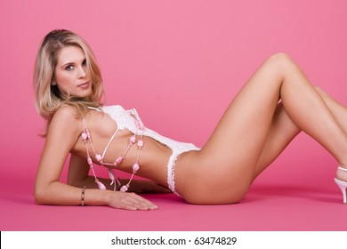 Sexy woman laying on pink background