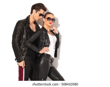 sexy woman in leather clothes standing near boyfriend with finger on her chin in studio