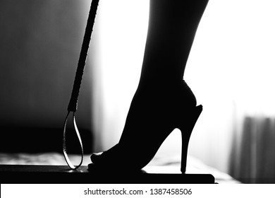 sexy woman leg and ridding crop. woman domination and foot fetish. sexy woman leg in high heel mules.