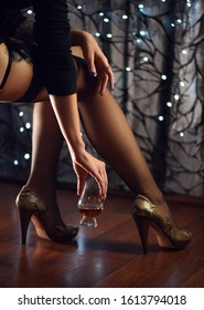 Sexy woman with legs in black stockings holding glass of whiskey