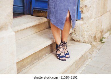 Sexy woman legs in blue suede leather sandals on the stairs. Woman wearing trendy long suede skirt and gladiators sandals. Fashionista walking on the city street, summer fashion look