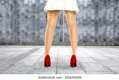 Sexy woman legs and red shoes with wall of free space