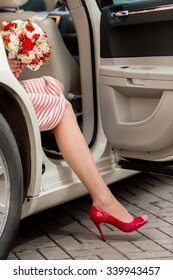 Sexy woman legs wearing red high heels sitting in a car, focus on shoes