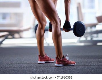 Sexy woman lifting barbell at the gym. Part of body, beautiful legs