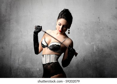 Sexy woman in lingerie holding a whip