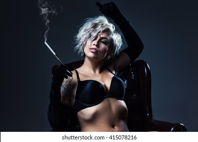Sexy woman in lingerie and long gloves posing in an antique chair, smoking.