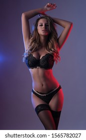 Sexy woman in lingerie in studio shoot with colorful lights.