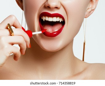 Sexy Woman lips with bloody lipstick. Fashion Glamour Halloween art design. Vampire girl getting ready to celebrate Halloween