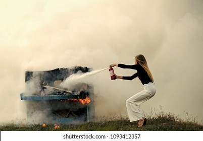 Sexy woman with long hair at piano on fire, Halloween. Music style and art. Fire and smoke on grunge instrument. Firefighting of girl with extinguisher. Burning piano and fashion woman at rock concert