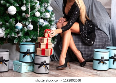 Sexy woman with long legs sitting by the Christmas tree