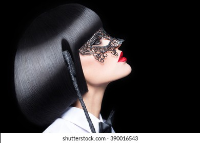 Sexy woman in mask holding whip at night, bdsm. Mask and tux outfit with red lips and cleopatra hair style.