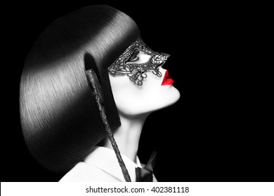 Sexy woman in mask holding whip at night, selective coloring. BDSM. Mask and tux outfit with red lips and cleopatra hair style.