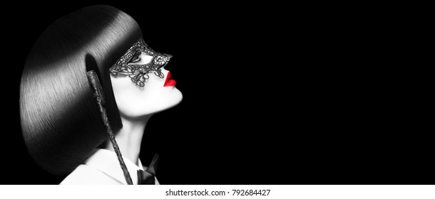 Sexy woman in mask holding whip at night, selective coloring banner. BDSM. Mask and tux outfit with red lips and cleopatra hair style.