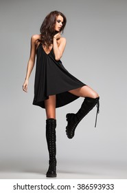 sexy woman model dressed in black dress and long boots in the studio