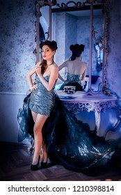 Sexy woman model  looking like a vampire, standing up and having a baroque mirror behind, indoors, with stiletto fingernails, silver cocktail dress with train. Maleficent lookalike concept