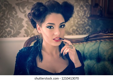 Sexy woman model looking like a vampire with a black stiletto nail between the teeth and looking straight on a couch, having sculpting make-up and cocktail dress . Maleficent lookalike retro concept