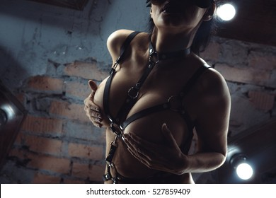 sexy woman with naked breast in leather belts. Close-up. Fetish, BDSM