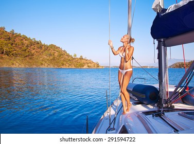 Sexy woman on sailboat, pretty girl with perfect body tanning on the deck of water transport, active beach holidays, enjoying summer vacation