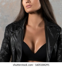 Sexy woman part of body, cleavage, black lingerie, leather jacket