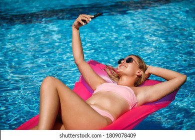 Sexy woman with a phone in a swimsuit lies on a pink inflatable mattress in the pool. Relax by the pool on a hot summer sunny day. Vacation concept