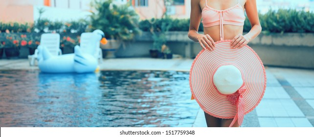 Sexy woman with pink bikini and hat in swimming pool, Caucasian girl is blonde long hair, Summer season concept