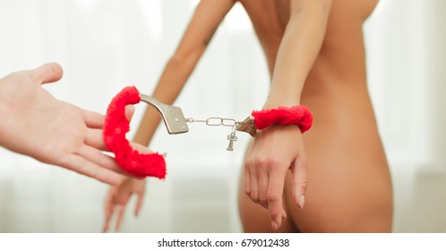 Sexy woman playing with macho lovers body in luxury flat, handcuffs and bdsm. Passionate couple kissing, boy and girl. Having sex. Young lovers. People in love. Positions kamasutra. Sexy couple.