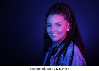 Sexy woman portrait in neon pink and blue light. Girl with dreadlocks in a nightclub, shining make-up with a highlighter. Glitter skin. Clubber, night life concept. Copy space.