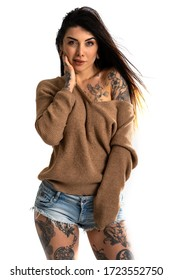 Sexy woman portrait with tattoo against white wall background.