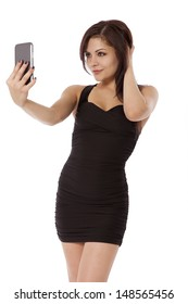 Sexy woman poses as she takes a picture of herself, isolated on a white background.