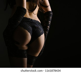 Sexy woman posing from behind in black laced lingerie. Boudoir fantasy image of sensual beatiful lady back in erotic underwear. Hot female model in net stockings garter belt panties and gloves