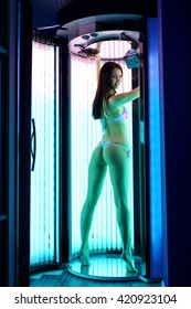 Sexy woman posing while tanning in modern solarium