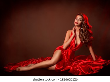 Sexy Woman Red Dress Fashion. Sensual Model lying in Slit Gown. Evening Make up and curly wavy Hairstyle. Copy Space