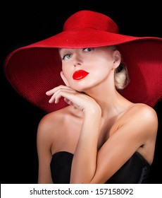 sexy woman in red hat with red lips looking at camera