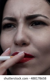Sexy woman with red lips smoking close up