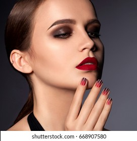 Sexy woman with red matte lips and nails with black stripes. The concept of expensive manicure. Smokey eye makeup, girl isolated on dark background