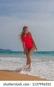 Sexy woman in red swimsuit stands with his back on the beach in water with small waves and smiling, Phuket, Thailand