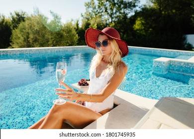 sexy woman relax in swimming pool outdoors. Beautiful female model in swimsuit drink champagne and eat fruits. Summer vacation time in luxury resort.