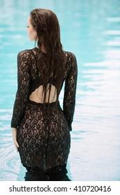Sexy woman relaxing in black fashion dress in pool. Creative photosessin of beautiful caucasian girl.