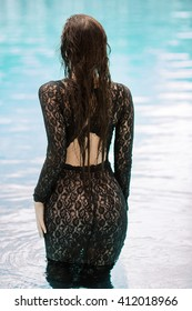Sexy woman relaxing in black fashion dress in pool. Creative photo session of beautiful Caucasian woman.