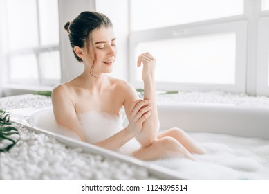 Sexy woman rubs the body with foam in the bath