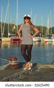 Sexy woman in sailor uniform posing in front of yachts