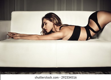 sexy woman in seductive black lingerie lying on a couch