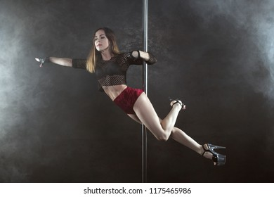 Sexy woman shows striptease on pole, she is gymnast.
