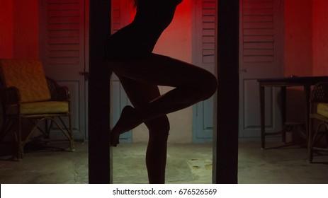Sexy Woman Silhouette Dancing at the Hotel. Pole Dancer female Stripper in the Night. Sensual Red light, noir style. Beautiful Dancing Girl with Sexy Body. Hot Erotic Private dance, striptease.