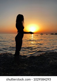 Sexy woman silhouette standing in the sand during a sunset on Golden bay, Malta